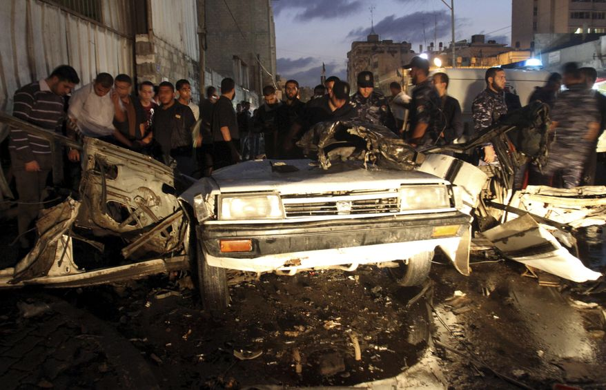 Palestinians gather around a destroyed car after an explosion in Gaza City, Wednesday, Nov. 17, 2010. Hamas officials say one person has been killed and four others wounded in the car explosion. Hamas media reported the car was hit in an air strike. Israeli military had no immediate comment.(AP Photo/ Hatem Moussa)