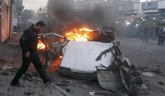 Palestinians gather around a destroyed car after an explosion in Gaza City, Wednesday, Nov. 17, 2010. Hamas officials say one person has been killed and four others wounded in the explosion. Hamas media reported the car was hit in an air strike. Israeli military had no immediate comment.(AP Photo/ Majed Hamdan)