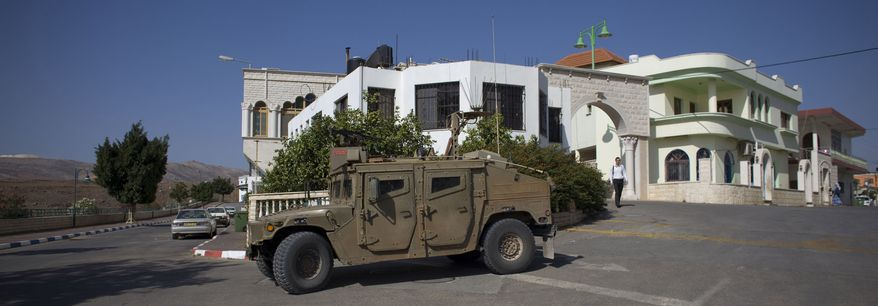 An Israeli army vehicle is seen in the village of Ghajar between northern Israel and Lebanon, Wednesday, Nov. 10, 2010. Israel's Prime Minister Benjamin Netanyahu presented a plan to U.N. Secretary-General Ban Ki-moon on Monday to withdraw from the northern half of Ghajar, recaptured during the 2006 war against Hezbollah guerrillas in Lebanon. (AP Photo/Tara Todras-Whitehill)