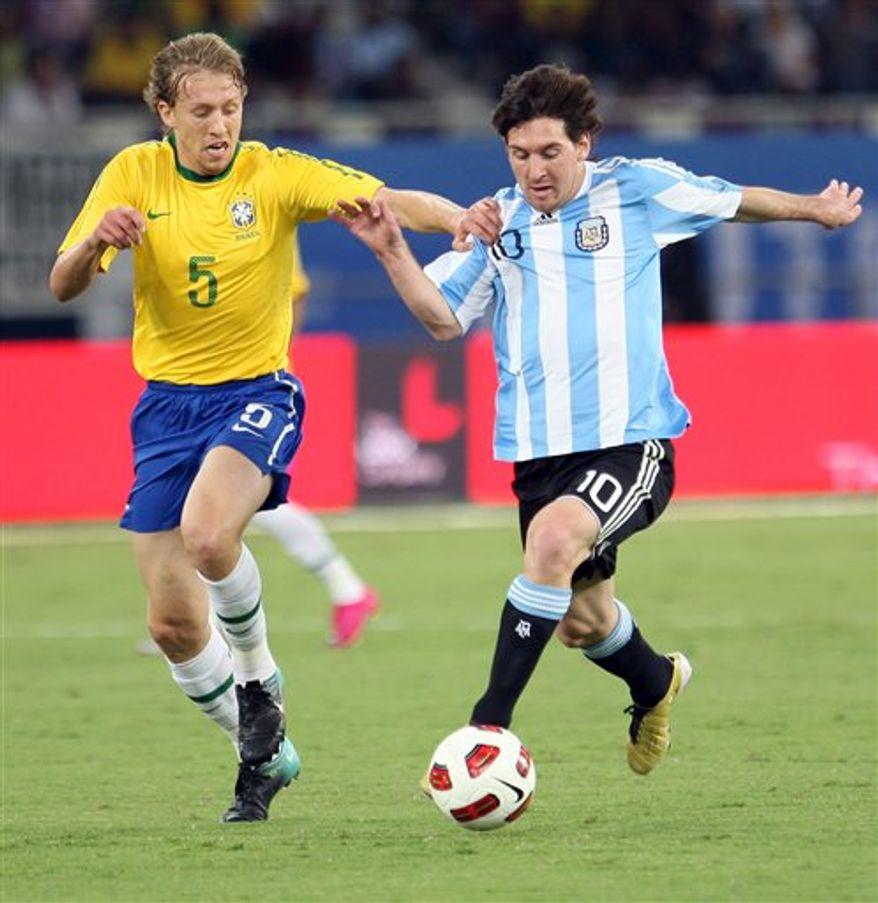Argentina's striker Lionel Messi (R) challenges Brazil's midfielder Lucas Leiva during their friendly soccer match at Khalifa Stadium in the Qatari capital Doha on Wednesday, Nov. 17, 2010 .(AP Photo/Osama Faisal)
