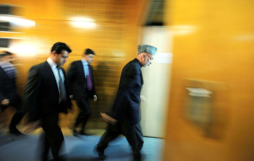 ASSOCIATED PRESS PHOTOGRAPHS Afghan President Hamid Karzai leads the way out of an auditorium after delivering a speech Nov. 6. His recent public remarks are puzzling his nation's allies.