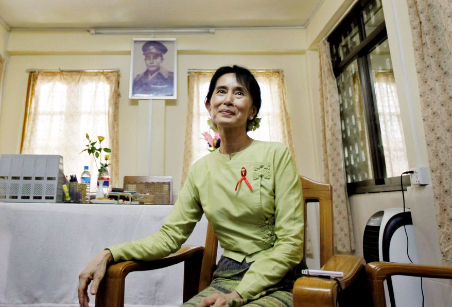 ASSOCIATED PRESS Burma's pro-democracy leader Aung San Suu Kyi pauses during an interview Thursday. A portrait of her father, independence hero Gen. Aung San, hangs on the wall at a democracy league office in Rangoon.