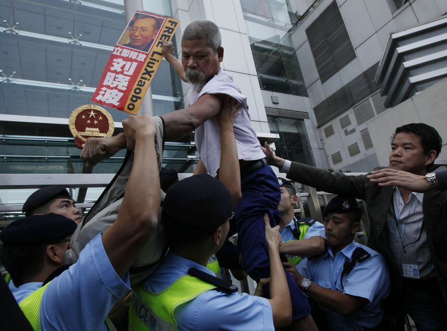 A pro-democracy protester holding the picture of the jailed Chinese dissident Liu Xiaobo, tries to climb across the police line during a demonstration at the China Liaison Office in Hong Kong Thursday, Nov. 11, 2010. The Norwegian Nobel Committee hopes Chinese authorities will allow the wife or some other close relative of imprisoned Nobel Peace Prize winner Liu Xiaobo to travel to Oslo and accept the award on his behalf. (AP Photo/Kin Cheung)
