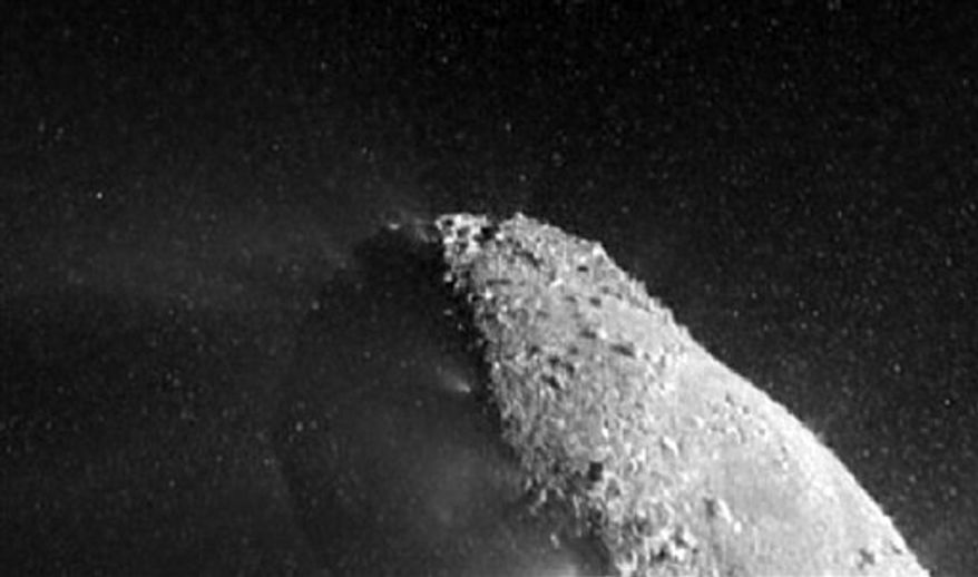 This image provided by NASA shows a Nov. 4, 2010 image from NASA's EPOXI mission spacecraft showing part of the nucleus of comet Hartley 2. The sun is illuminating the nucleus from the right. A distinct cloud of individual particles is visible. Scientists say a NASA spacecraft braved a cosmic ice storm during this recent flight past the comet Hartley 2.(AP Photo/NASA)