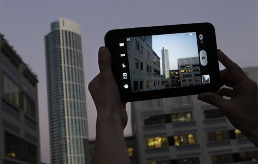An Associated Press reporter demonstrates the Samsung Galaxy Tab during a product review in San Francisco, Tuesday, Nov. 16, 2010. (AP Photo/Jeff Chiu)