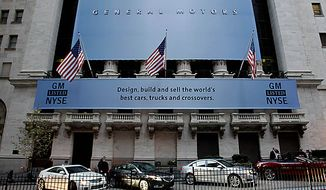 General Motors' cars are lined up in front of the New York Stock Exchange in New York, Thursday, Nov. 18, 2010.  (AP Photo/Seth Wenig)