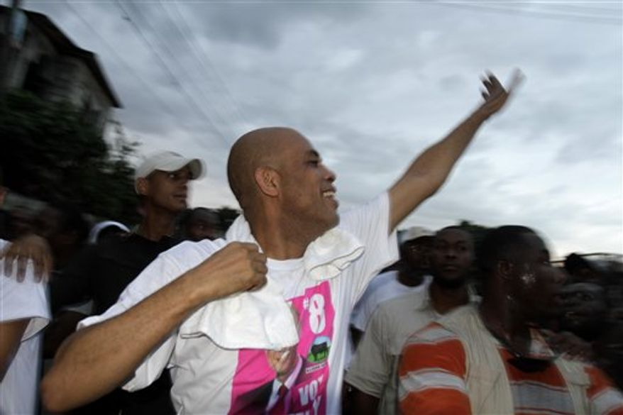 "Presidential candidate and singer Michel ""Sweet Micky"" Martely  gestures during a campaign rally in Croix-Des-Bouquets, Haiti, Friday, Nov 12, 2010. Less that two weeks to go before the election, a rapidly spreading cholera outbreak is infecting even the presidential campaign.(AP Photo/Dieu Nalio Chery)"