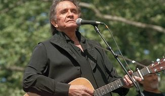 Johnny Cash performs at a benefit concert in Central Park in New York on May 23, 1993.   (Associated Press) **FILE**