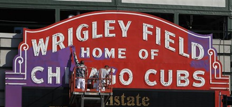 Painters Bill Barnoski, left, and Mike Kwiatkowski with the National Decorating Co. paint the historic Wrigley Field marquee from red to Northwestern University purple Monday, Nov. 15, 2010 in Chicago. Northwestern will host Illinois for a Big Ten Conference game Sat. Nov. 20. (AP Photo/Charles Rex Arbogast)