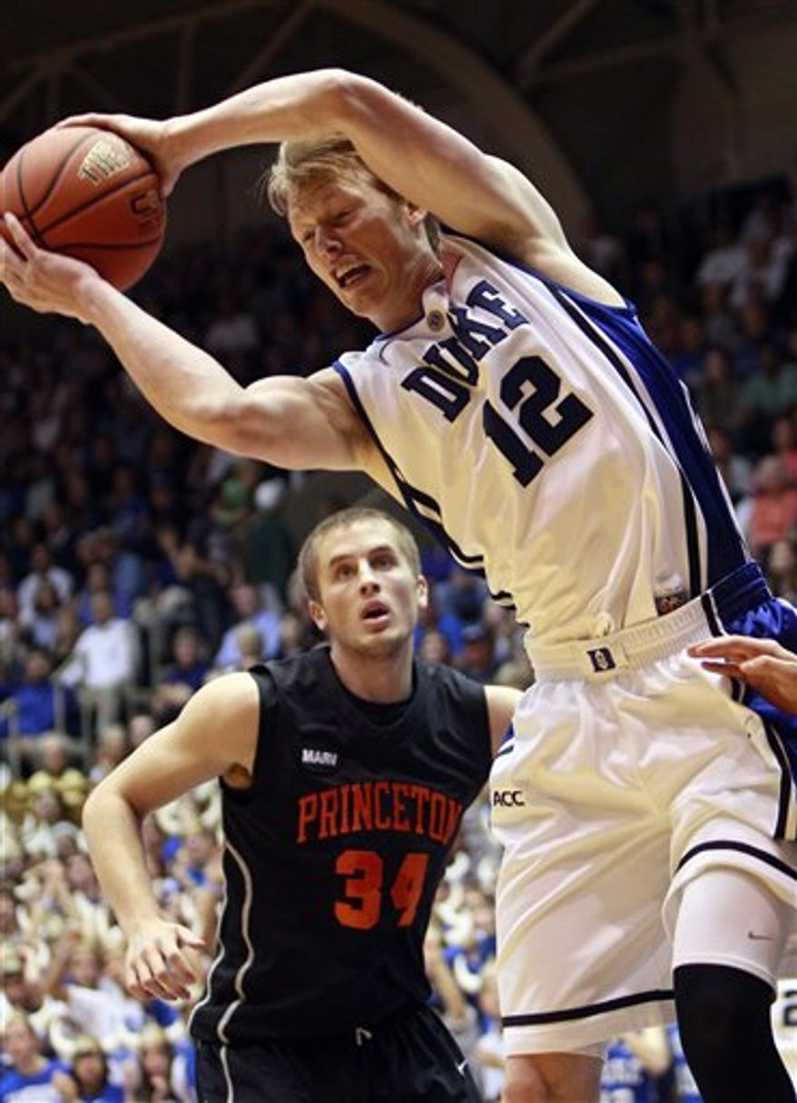 Duke's Kyle Singler (12) pulls down a rebound over Princeton's Ian Hummer (34) during the first half of an NCAA college basketball game in Durham, N.C., Sunday, Nov. 14, 2010. (AP Photo/Gerry Broome)