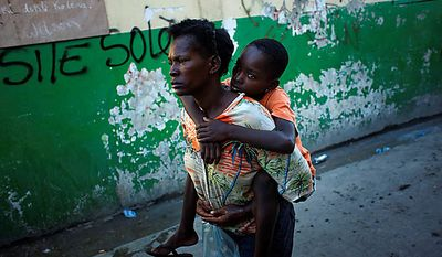 A boy suffering cholera symptoms is carried by a relative to the St. Catherine hospital, run by Doctors Without Borders, in the slum of Cite Soleil in Port-au-Prince, Haiti, Thursday, Nov. 18, 2010. A month-old cholera epidemic has killed at least 1,000 people and hospitalized thousands.(AP Photo/Emilio Morenatti)