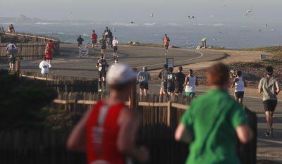 Macdonald Ondara, in orange, of Kenya runs back from Asilomar State Beach on his way to winning the men's division of the Big Sur Half Marathon in Pacific Grove, Calif., on Sunday, Nov. 14, 2010. (AP Photo/ Monterey County Herald, David Royal)