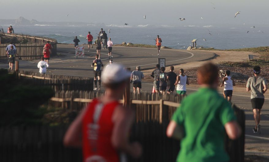 Macdonald Ondara, in orange, of Kenya runs back from Asilomar State Beach on his way to winning the men's division of the Big Sur Half Marathon in Pacific Grove, Calif., on Sunday, Nov. 14, 2010. (AP Photo/ Monterey County Herald, David Royal)