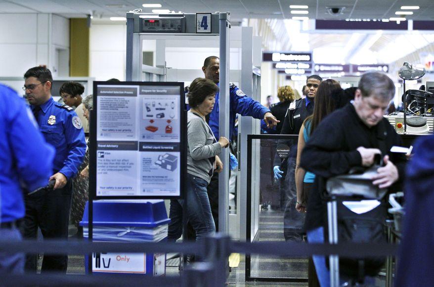 Transportation Security Administration officers (in blue uniforms) screen airline passengers at Ronald Reagan Washington National Airport on Monday, Nov. 15, 2010. (AP Photo/Manuel Balce Ceneta)