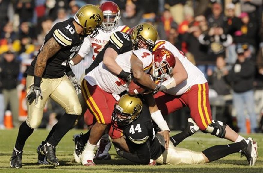In this photo taken Nov. 13, 2010, Colorado's Patrick Mahnke, top center, and Nick Kasa, bottom, sack Iowa State's Austen Arnaud (4) as the ball is forced out and returned for a Colorado touchdown in the fourth quarter of a NCAA college football game in Boulder, Colo  Arnaud suffered a season ending knee injury on the play.  (AP Photo/ Matt McClain)
