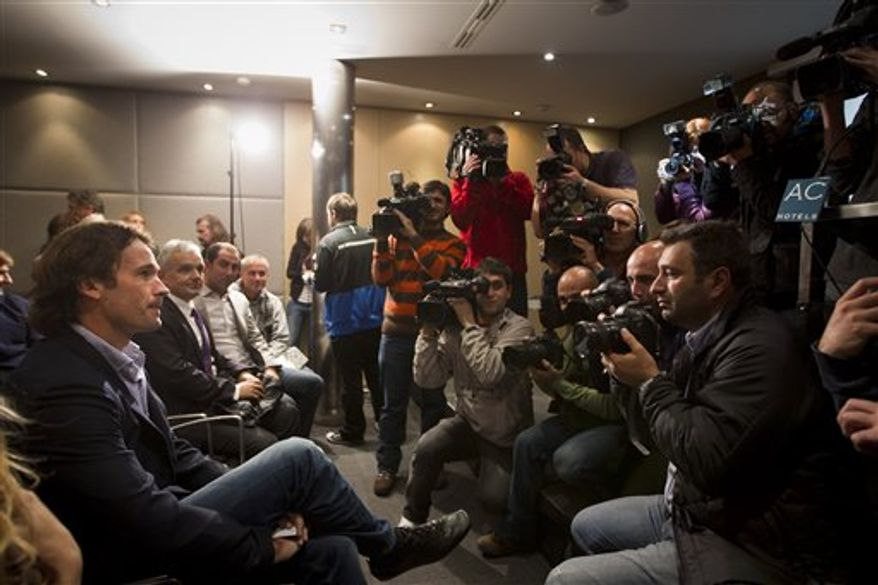 Former French Open champion Carlos Moya, left, attends a press conference  in Madrid, Wednesday, Nov. 17, 2010. Moya, 34, a former No. 1 and member of Spain's 2004 Davis Cup-winning team, announced his retirement from tennis citing a nagging foot injury,  calling time on a 15-year career.(AP Photo/Daniel Ochoa de Olza)