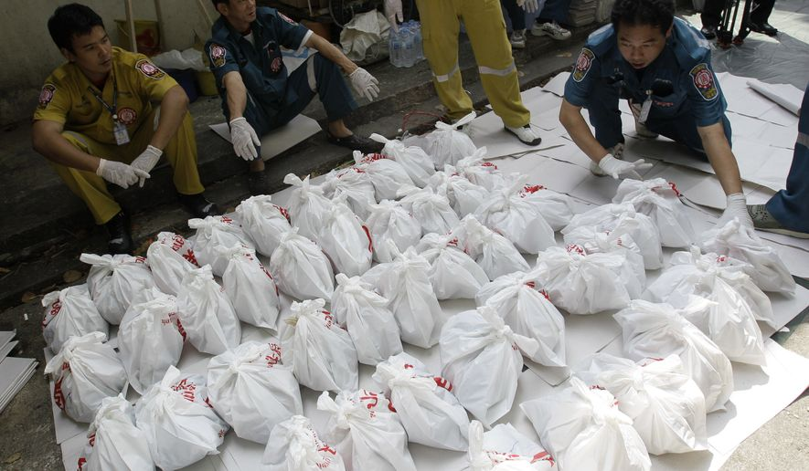 Rescue workers arrange bags containing dead fetuses found at the morgue of a Buddhist temple in Bangkok, Thailand, Friday, Nov. 19, 2010. Thai police have discovered hundreds of human fetuses dumped at the morgue during an investigation that began Tuesday. (AP Photo/Sakchai Lalit)