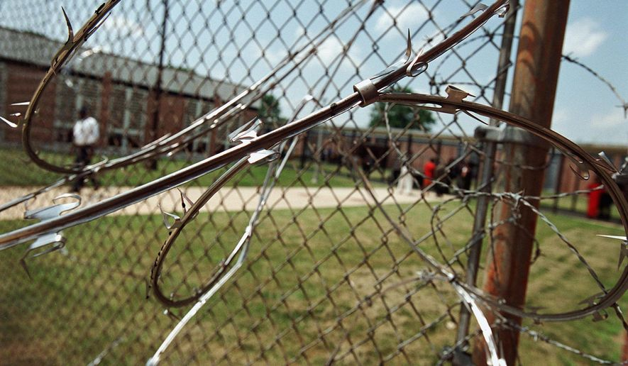 THE WASHINGTON TIMES Razor wire wraps around a fence at Oak Hill Academy, which was closed by a D.C. Council mandate.