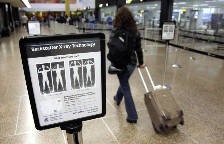 **FILE** In this photo from Nov. 19, a passenger walks past a sign informing travelers about the use of full-body scanners for TSA security screening at Seattle-Tacoma International Airport in Seattle. (Associated Press)