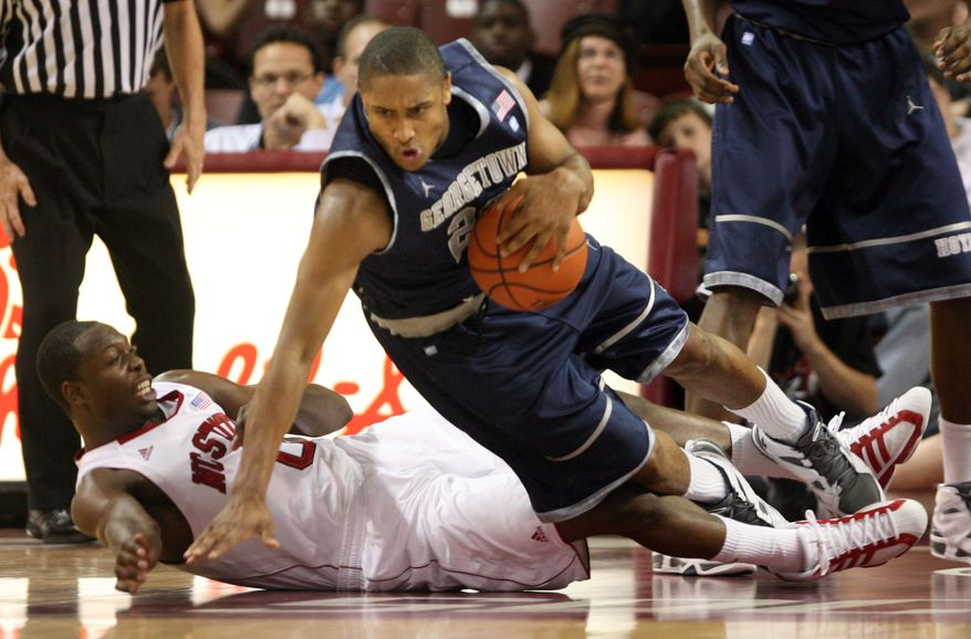 ASSOCIATED PRESS Georgetown's Jerrelle Benimon, at right, falls over N.C. State's DeShawn Painter during first-half NCAA college championship game action during the ESPN Charleston Classic basketball tournament at the Carolina First Arena in Charleston, S.C., Sunday, Nov. 21, 2010.