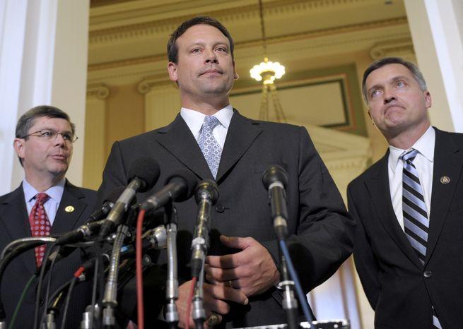 **FILE** Rep. Heath Shuler, North Carolina Democrat (center), accompanied by Reps. Mike Ross, Arkansas Democrat (left), and Jim Matheson, Utah Democrat, speaks to reporters on Capitol Hill on Nov. 17. (Associated Press)