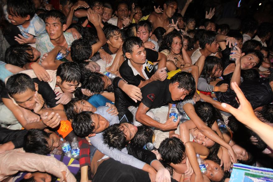People are pushed onto a bridge Monday, the last day of a water festival in Phnom Penh, Cambodia. At least 339 died in the panic. (Associated Press)