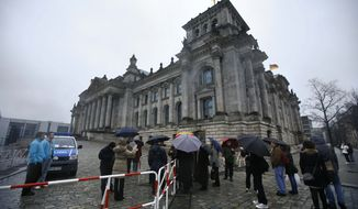 Visitors stand at a security fence in front of the Reichstag building, Germany's house of parliament, in Berlin on Monday, Nov. 22, 2010. (AP Photo/Markus Schreiber)