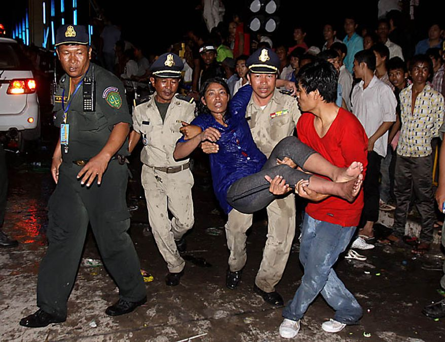 An injured Cambodian is carried by police and other visitors after a  stampede onto a bridge at an accident site during the last day of celebrations of the water festival in Phnom Penh, Cambodia, Monday, Nov. 22, 2010. Thousands of people celebrating a water festival on a small island in a Cambodian river stampeded Monday evening, killing many people, a hospital official said. Hundreds more were hurt as the crowd panicked and pushed over the bridge to the mainland. (AP Photo/Heng Sinith)