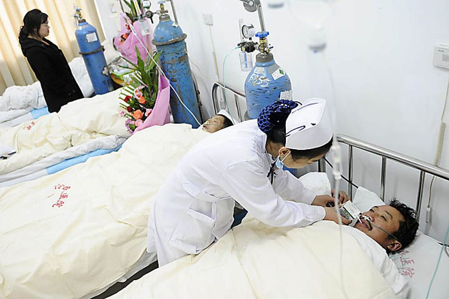 In this photo released by China's Xinhua News Agency, a nurse takes care of a rescued miner at a hospital in Weiyuan County, southwest China's Sichuan Province, Monday, Nov. 22, 2010. All 29 miners were pulled out of a Chinese coal mine Monday after being trapped by a flood and waiting a day for rescuers to pump out water. (AP Photo/Xinhua, Jiang Hongjing)