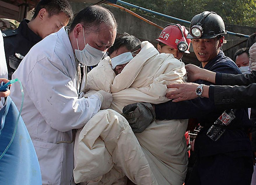 Rescuers carries a trapped miner wrapped in white quilts out from the flooded Batian Coal Mine in Xiaohe town of Weiyuan county in southwest China's Sichuan province Monday, Nov. 22, 2010. Emergency crews drained the flooded Chinese coal mine and rescued all 29 trapped workers Monday, ending a daylong rescue drama. (AP Photo/Color China Photo)