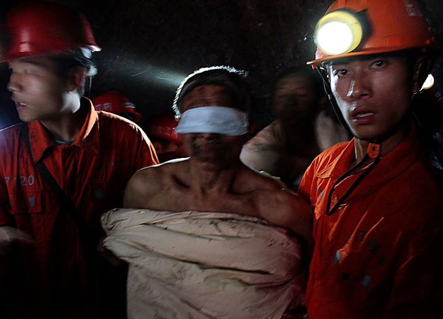 Rescuers escort a trapped miner wrapped in white quilt on their way out from the flooded Batian Coal Mine in Xiaohe town of Weiyuan county in southwest China's Sichuan province Monday, Nov. 22, 2010. Emergency crews drained the flooded Chinese coal mine and rescued all 29 trapped workers Monday, ending a daylong rescue drama. (AP Photo/Color China Photo)