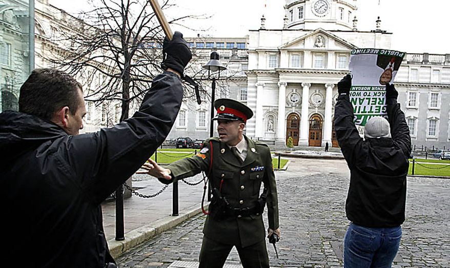 A Irish Army Military police officer confronts Sinn Fein protesters who broke through the gates at goverNment buildings, Dublin, Ireland, Monday, Nov. 22, 2010 as they called for the Irish Prime Minister to resign. Ireland's banks will be pruned down, merged or sold as part of a massive EU-IMF bailout, the government says as a shellshocked nation comes to grips with its failure to protect its financial institutions.  (AP Photo/Peter Morrison)