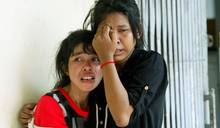 Relatives cry at Preah Kossamak Hospital, where the bodies of stampede victims are laid, in Phnom Penh, Cambodia, on Tuesday. (Associated Press)