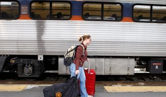 HOLIDAY RUSH: A passenger at Washington's Union Station hurries to catch a train Tuesday as other travelers make plans to head for area airports Wednesday. (Associated Press)