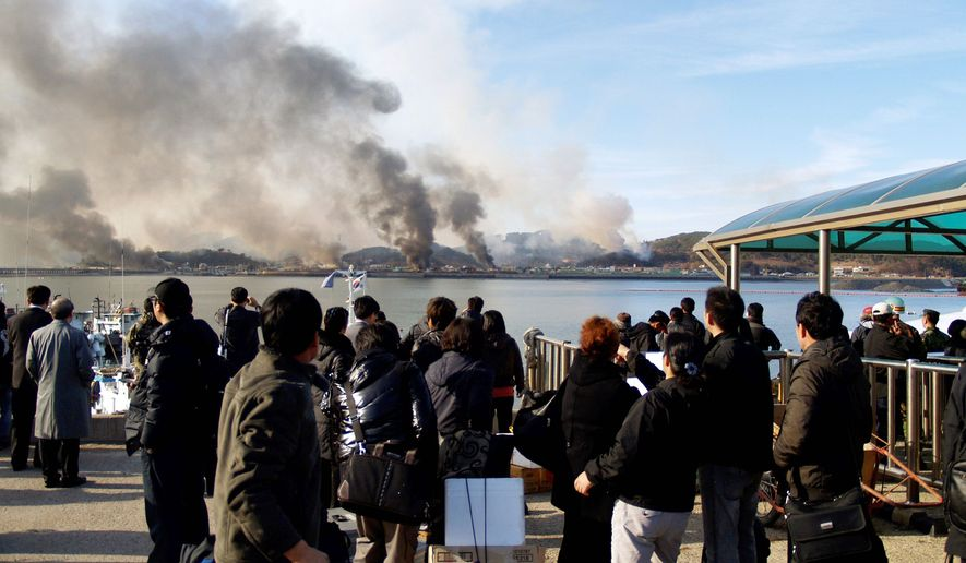 BRINK OF WAR: South Koreans watch smoke rising from South Korea's Yeonpyeong Island near the border with North Korea on Tuesday. The North fired artillery barrages onto the island. South Korea returned fire and launched fighter jets. (Associated Press)