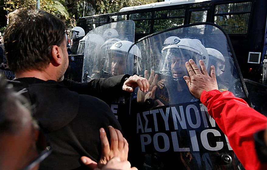 Municipal workers scuffle with riot police in Athens, Tuesday, Nov. 23, 2010. Mounds of rubbish have piled up on the streets of the Greek capital, as the strike by municipal employees against wage cuts and planned layoffs of contract workers entered its fifth day Tuesday. Greece will receive the next part of its euro110 billion ($150 billion) bailout package, but still faces challenges in its reforms and must make an extra effort to meet next year's deficit targets, the IMF, ECB and EU executive said Tuesday. (AP Photo/Alkis Konstantinidis)
