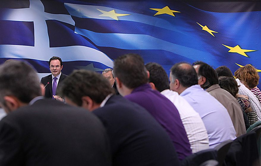 Greek Finance Minister George Papaconstantinou, seen behind journalists, speaks during a news conference in Athens, on Tuesday, Nov. 23, 2010. Greece is broadly on track with reforms needed to continue tapping a euro 110 billion ($150 billion) bailout package, but still faces challenges and must make an extra effort to meet deficit reduction targets, the IMF, ECB and EU executive said Tuesday. (AP Photo/Petros Giannakouris)