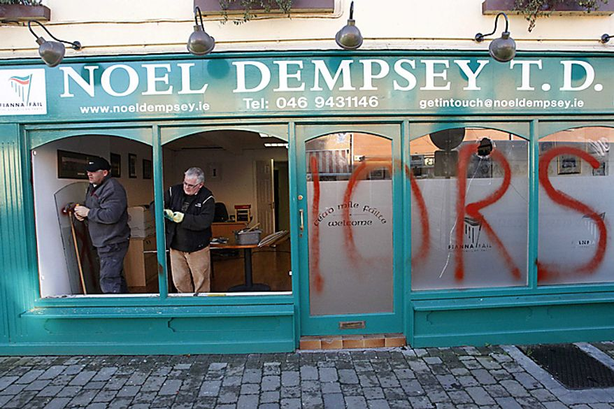 Workmen repair the office of Ireland's Transport Minister Noel Dempsey after it was was vandalised and painted with the words: 'traitors' in the village of Trim, 30 miles north west of Dublin, Ireland, Tuesday, Nov. 23, 2010. Lawmakers in Prime Minister Brian Cowen's own party mounted a rebellion Tuesday to try to oust him, an effort that could trigger a snap election and delay a massive EU-IMF bailout of Ireland. Dempsey is one of Cowen's loyal lieutenants. (AP Photo/Peter Morrison)