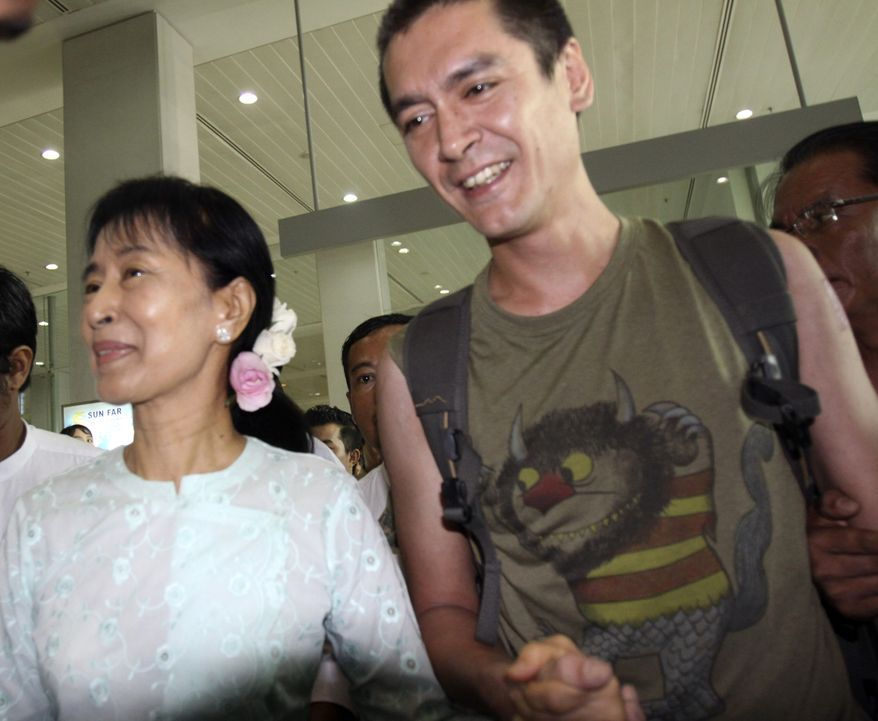 Burma's pro-democracy leader Aung San Suu Kyi holds the hands of her son Kim Aris, right, as they leave Rangoon International Airport  Tuesday, Nov. 23, 2010. (AP Photo/Khin Maung Win)