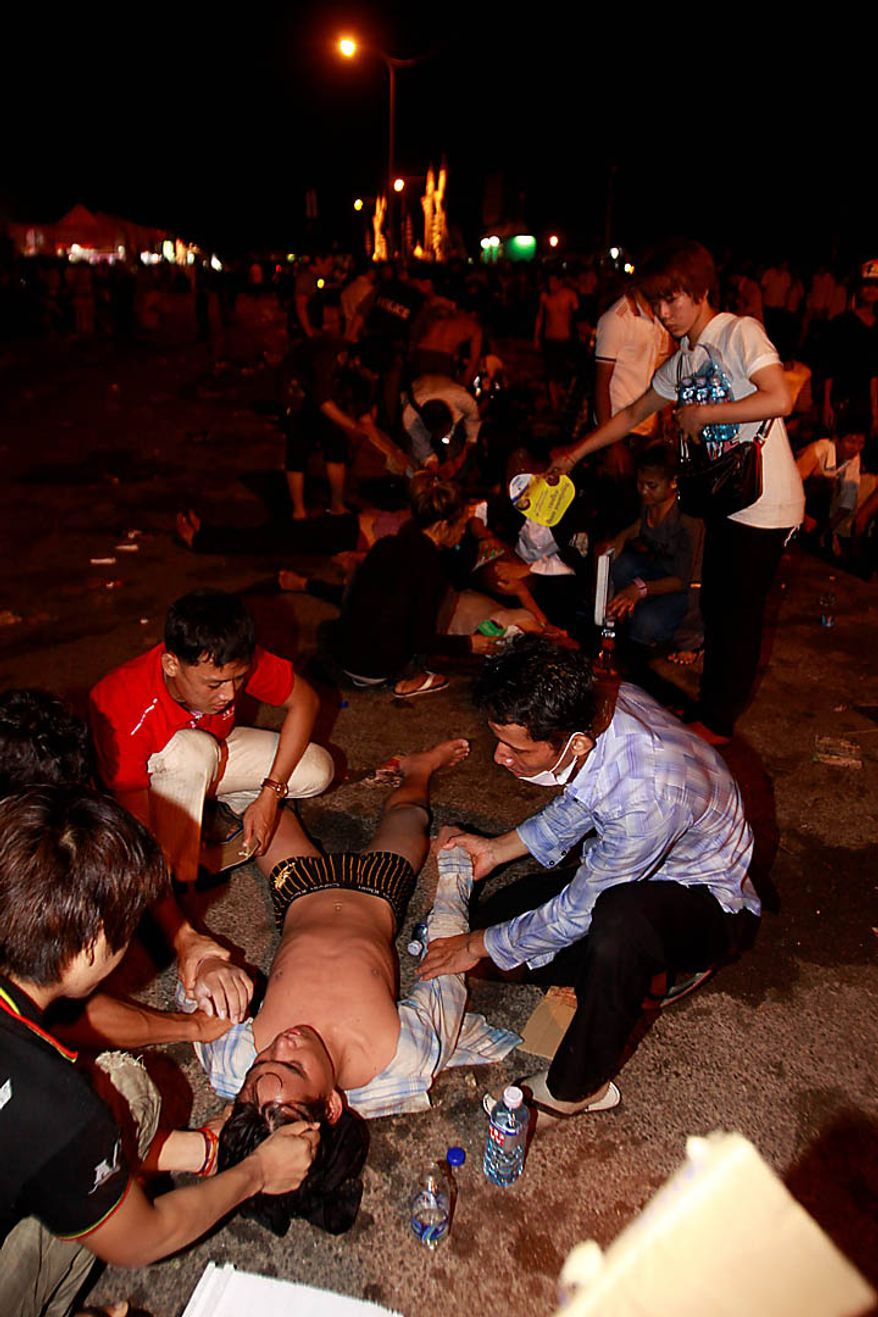An injured Cambodian is helped by other visitors after a  stampede onto a bridge at an accident site during the last day of celebrations of the water festival in Phnom Penh, Cambodia, Monday, Nov. 22, 2010. Thousands of people celebrating a water festival on a small island in a Cambodian river stampeded Monday evening, killing many people, a hospital official said. Hundreds more were hurt as the crowd panicked and pushed over the bridge to the mainland. (AP Photo/Heng Sinith)
