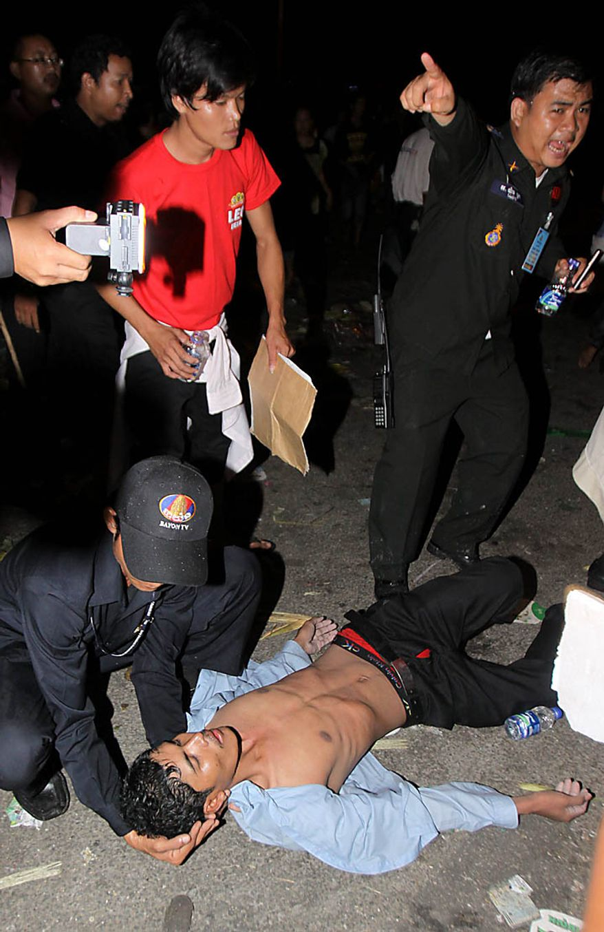 An injured Cambodian is helped by a police officer after a  stampede onto a bridge at an accident site during the last day of celebrations of the water festival in Phnom Penh, Cambodia, Monday, Nov. 22, 2010. Thousands of people celebrating a water festival on a small island in a Cambodian river stampeded Monday evening, killing many people, a hospital official said. Hundreds more were hurt as the crowd panicked and pushed over the bridge to the mainland. (AP Photo/Heng Sinith)