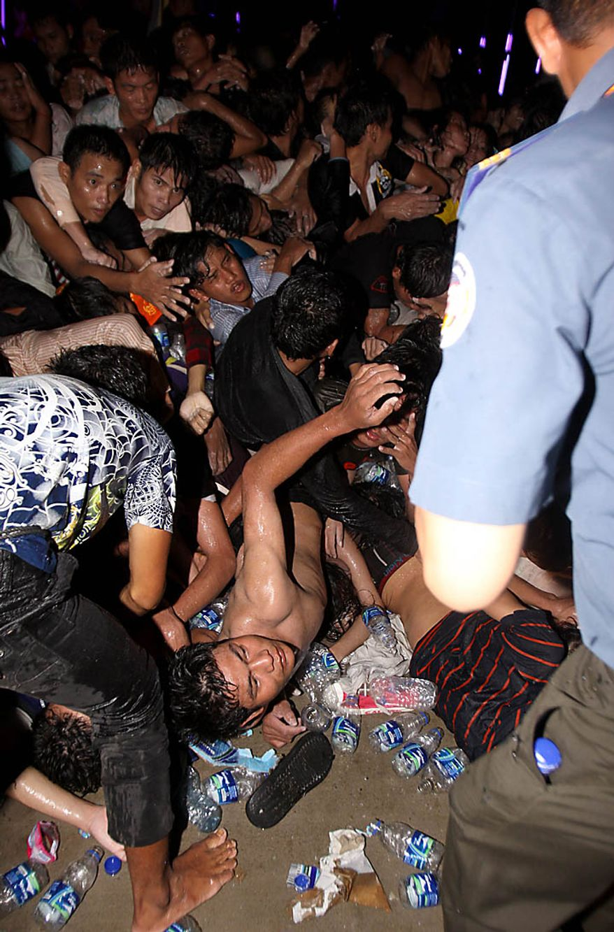 An injured Cambodian seeks help after a  stampede onto a bridge during the last day of celebrations of the water festival in Phnom Penh, Cambodia, Monday, Nov. 22, 2010. Thousands of people celebrating a water festival on a small island in a Cambodian river stampeded Monday evening, killing many people, a hospital official said. Hundreds more were hurt as the crowd panicked and pushed over the bridge to the mainland. (AP Photo/Heng Sinith)