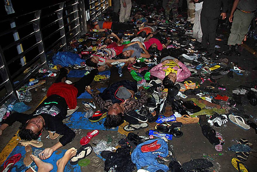 The bodies and belongings of Cambodians, who died in a stampede, lie on a bridge in Phnom Penh, Cambodia, Tuesday, Nov. 23, 2010. Thousands of people stampeded during a festival in the Cambodian capital Monday night, leaving more than 330 dead and hundreds injured in what the prime minister called the country's biggest tragedy since the 1970s reign of terror by the Khmer Rouge. (AP Photo/Philip Heijmans)