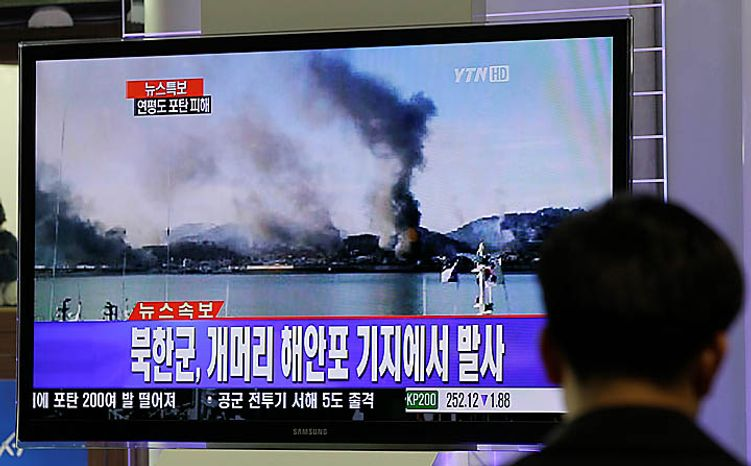 A South Korean man watches a TV screen showing smoking from South Korea's Yeonpyeong island near the border of North Korea, at Seoul train station Tuesday, Nov. 23, 2010. North Korea shot dozens of rounds of artillery onto the  populated South Korean island near their disputed western border Tuesday, military officials said, setting buildings on fire and prompting South Korea to return fire and scramble fighter jets. (AP Photo/Lee Jin-man)