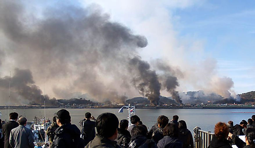 South Korean villagers watch smoke from South Korea's Yeonpyeong island near the border against North Korea Tuesday, Nov. 23, 2010. North Korea fired artillery barrages onto the South Korean island near their disputed border Tuesday, setting buildings alight and prompting South Korea to return fire and scramble fighter jets. (AP Photo/Yonhap)