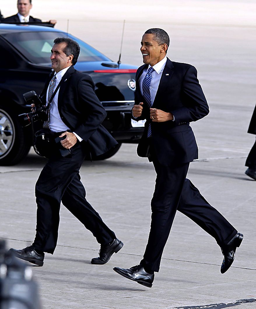 President Barack Obama jogs across the tarmac to greet supporters after he arrived on Air Force One at Grissom Air Reserve Base in Peru, Ind., Tuesday, Nov. 23, 2010. White House photographer Pete Souza is at left. (AP Photo/Michael Conroy)