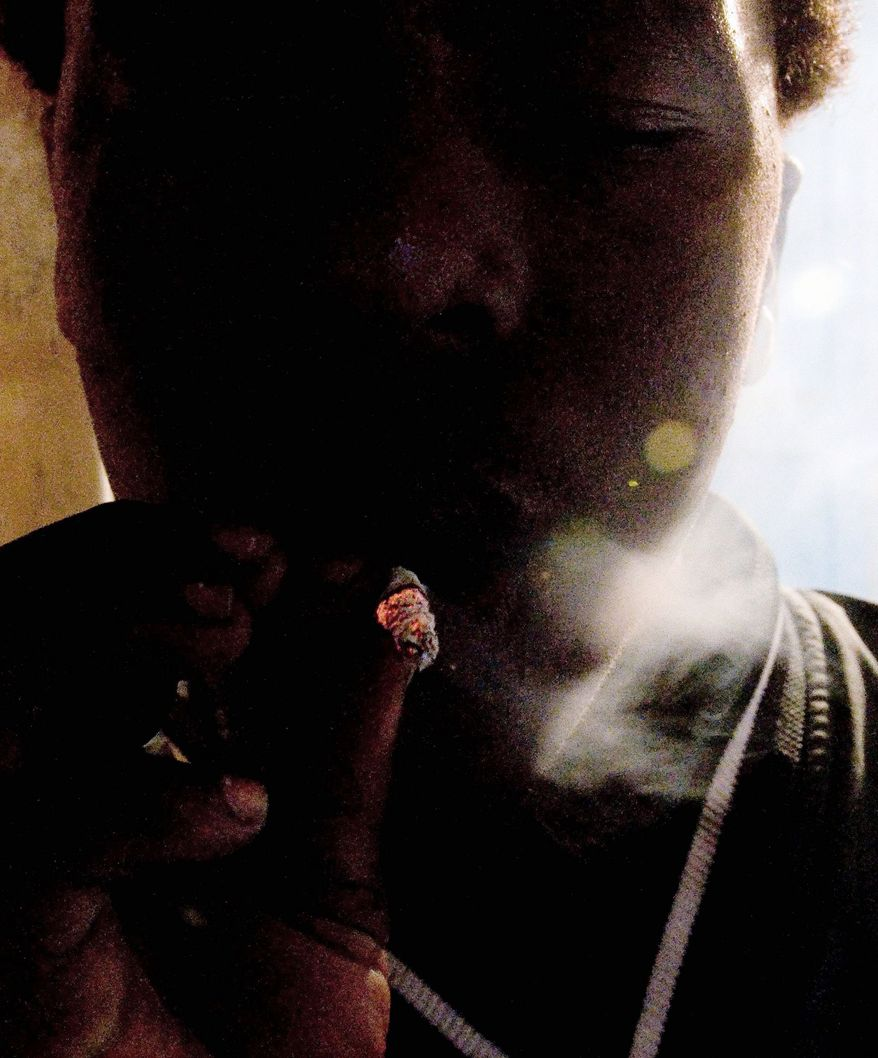 """An unidentified man smokes a concoction called """"whoonga"""" in the Kwadebeka Township. The concoction is called """"whoonga,"""" and it adds a bizarre twist to the war on AIDS in the world's worst-affected country just as it embarks on a massive distribution of medications. (Associated Press)"""