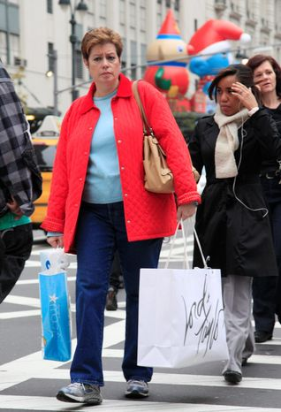 A shopper walks in New York on Tuesday with bags from Macy's and Lord & Taylor. (Associated Press)