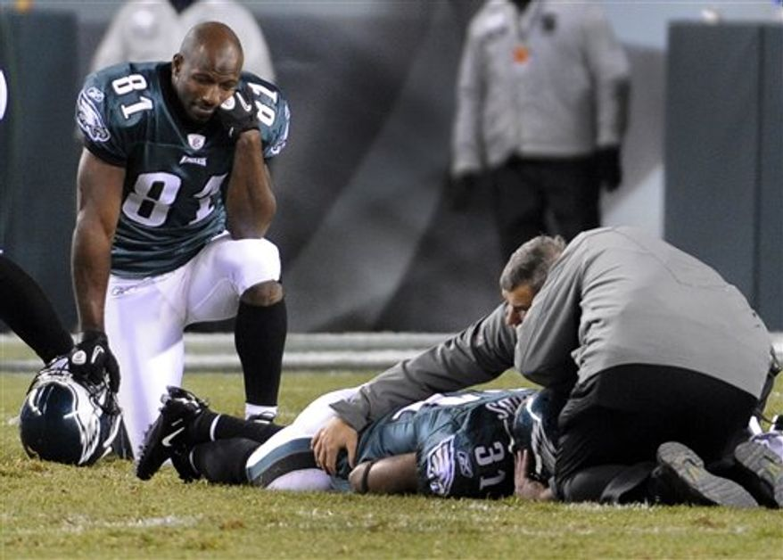 Philadelphia Eagles wide receiver Jason Avant kneels next to his teammate cornerback Ellis Hobbs as he is looked at after an injury during the second half of an NFL football game against the New York Giants in Philadelphia, Sunday, Nov. 21, 2010. (AP Photo/Miles Kennedy)
