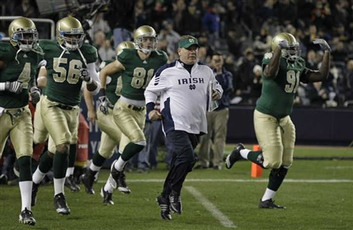 Notre Dame coach Brian Kelly runs on the field ahead of his team before the start of an NCAA college football game against Army at Yankee Stadium in New York, Saturday, Nov. 20, 2010.  (AP Photo/Kathy Willens)